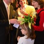 Děkan FF UK doc. PhDr. Michal Stehlík, Ph.D., předává kytici spoluorganizátorce výstavy Mgr. Karolíně Chundelové; v pozadí Jáchym Šerých, autor výtvarného a architektonického řešení výstavy