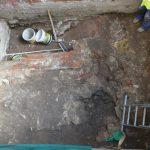 dno šachty; patrné základy dříve zde stojícího domu